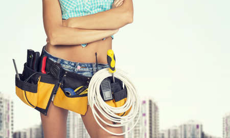 cropped image: Woman in tool belt with different tools standing crossed arms. Cropped image. Buildings as backdrop