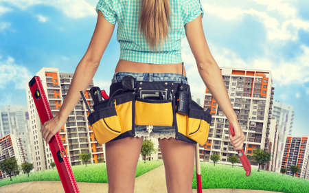 cropped image: Woman in tool belt with different tools stands back, holding building level and wrench. Cropped image. Green hill with road and buildings on background