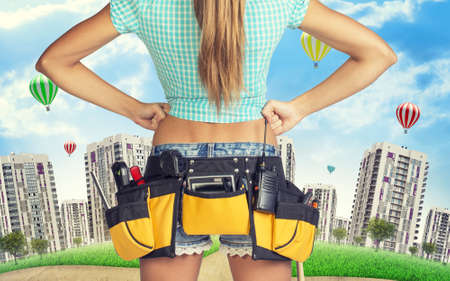 cropped image: Woman in tool belt with different tools stands back, akimbo. Cropped image. Green hill with buildings on background