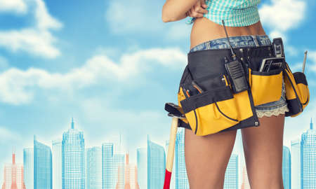 cropped image: Woman in tool belt with different tools stands back, crossed arms. Cropped image. Wire-frame buildings as backdrop