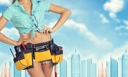cropped image: Woman in tool belt with different tools stands back, hands on hips. Cropped image. Wire-frame buildings as backdrop