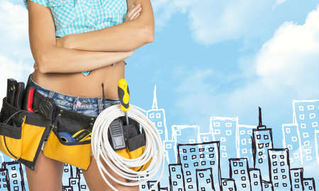 cropped image: Woman in tool belt with different tools, crossed arms. Cropped image. Sketch buildings as backdrop