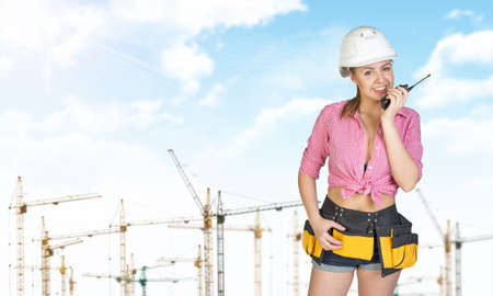 Woman in helmet and tool belt using on portable radio, smiling. Tower crane as backdrop photo