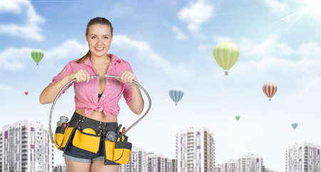 Woman in tool belt with different tools connects two flexible hoses, smiling. Buildings with air balloons as backdrop photo