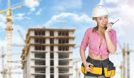 Woman in helmet and tool belt talking on portable radio, smiling. Construction site as backdrop photo