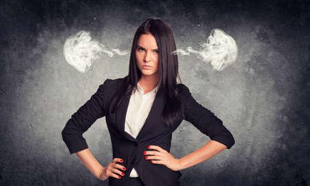 mujer enojada: Pared gris de hormigón con fisura. Mala mujer en juego con el vapor de los oídos Foto de archivo