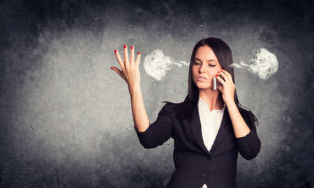 brunete: Concrete gray wall with fissure. Expressive woman in suit with steam from ears, talking on phone