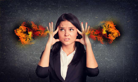 brunete: Concrete gray wall with fissure. Experiencing woman with fire from ears Stock Photo