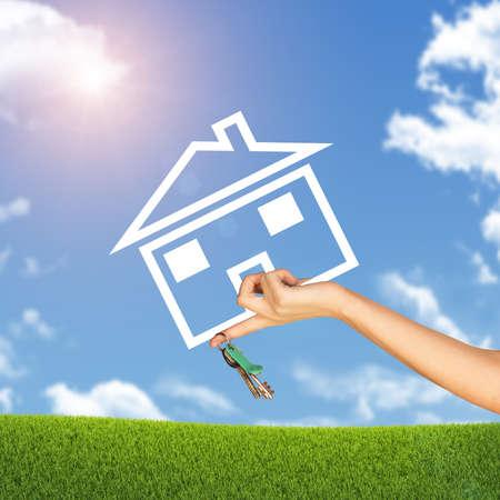 clave sol: Mano que sostiene el icono de la casa y llave. Fondo de cielo azul, las nubes y el sol, la hierba verde