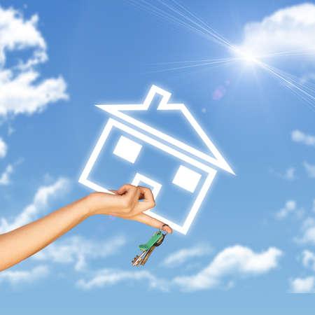 llave de sol: Mano que sostiene el icono de la casa y llave. Fondo de cielo azul, las nubes y sol Foto de archivo
