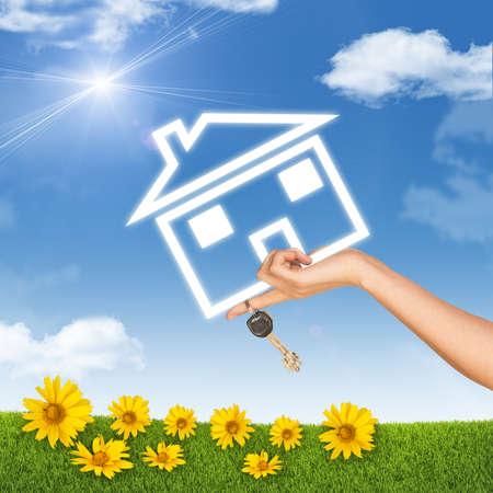 clave sol: Mano que sostiene el icono de la casa y llave. Fondo del cielo azul, las nubes y el sol, girasol, la hierba verde