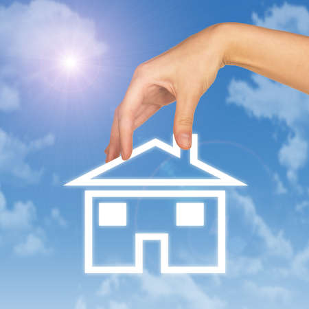 hand holding house: Hand holding house icon. Background of blue sky, clouds and sun Stock Photo