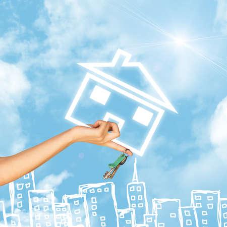 llave de sol: Mano que sostiene el icono de la casa y llave. Fondo de cielo azul, las nubes y sol, edificios de boceto Foto de archivo