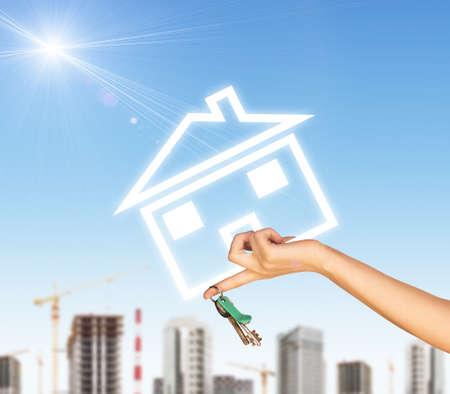 llave de sol: Mano que sostiene el icono de la casa y llave. Fondo del cielo azul, las nubes y el sol, borroneada edificios y chimeneas Foto de archivo