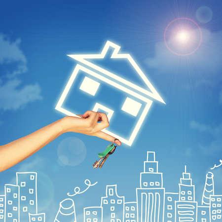 clave sol: Mano que sostiene el icono de la casa y llave. Fondo de cielo azul, las nubes y sol, bocetos de edificios Foto de archivo