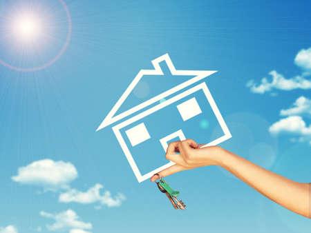 clave sol: Mano que sostiene el icono de la casa y llave. Fondo de cielo azul, las nubes y sol Foto de archivo