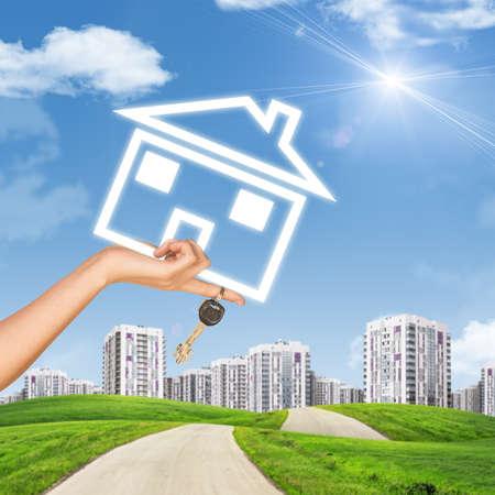 clave sol: Mano que sostiene el icono de la casa y llave. Fondo de cielo azul, las nubes y el sol, la construcci�n de carreteras y la falta de definici�n
