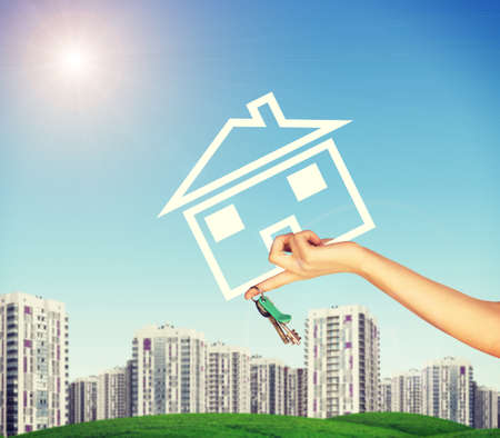 hand holding house: Hand holding house icon and key. Background of blue sky, clouds and sun, blured buildings Stock Photo