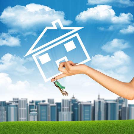 clave sol: Mano que sostiene el icono de la casa y llave. Fondo de cielo azul, las nubes y sol, edificios borroneada Foto de archivo