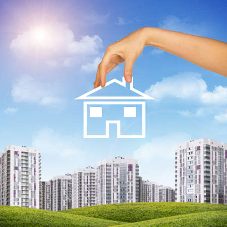 hand holding house: Hand holding house icon. Background of blue sky, clouds and sun, blured buildings Stock Photo