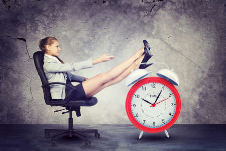 Woman in jacket and skirt sitting on chair. Put your feet on the alarm clock.