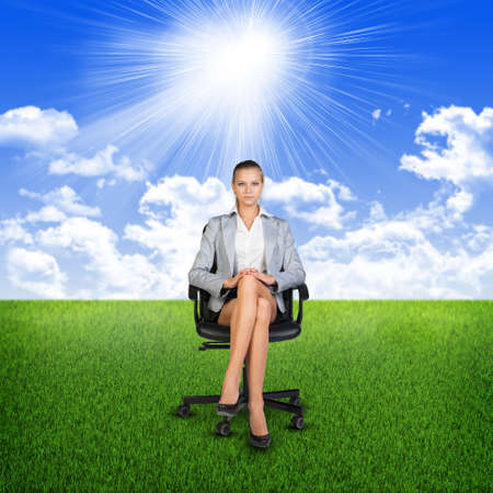 sits on a chair: Woman in jacket sits on chair. Background of grass, clouds and sun