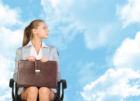 Business woman in skirt, blouse and jacket, sitting on chair. Against background of blue sky and clouds photo