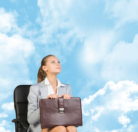 Business woman in skirt, blouse and jacket, sitting on chair and holding briefcase. Against background of blue sky and clouds photo