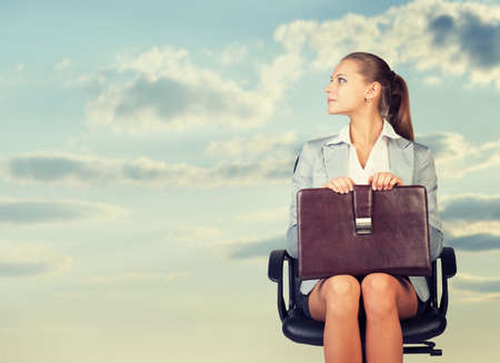 Business woman in skirt, blouse and jacket, sitting on chair and holding briefcase. Against background of sky and clouds photo