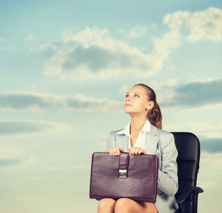 Business woman in skirt, blouse and jacket, sitting on chair. Against background of sky and clouds photo