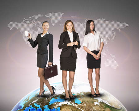 skirts: Business womens in suits, blouses, skirts, smiling and looking at camera. Against background of world map and globe.   Stock Photo