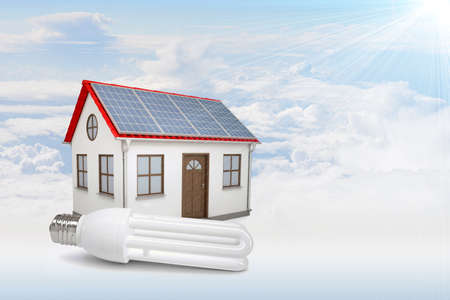 socle: White house with red roof, brown door and solar panels in clouds. Background sun shines brightly on large clouds