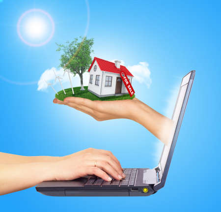 sun screen: White shack in hand with red roof, brown door and chimney of screen laptop. Hands typing on keyboard. Background sun shines brightly on left. Blue sky