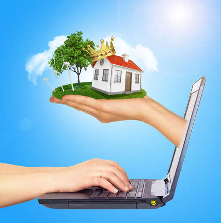 sun screen: White house for sale with red roof in hand , crown and chimney of screen laptop. Hands typing on keyboard. Background sun shines brightly on right. Blue sky Stock Photo