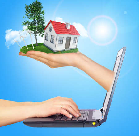 sun screen: White shack in hand with red roof, brown door and chimney of screen laptop. Hands typing on keyboard. Background sun shines brightly on right. Blue sky Stock Photo