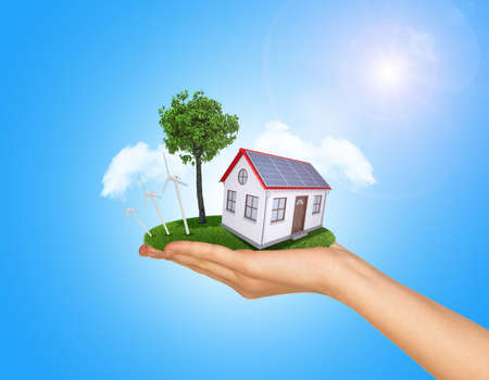 Hand holding house on green grass with tree, wind turbine and solar panels. Background clouds and blue sky photo