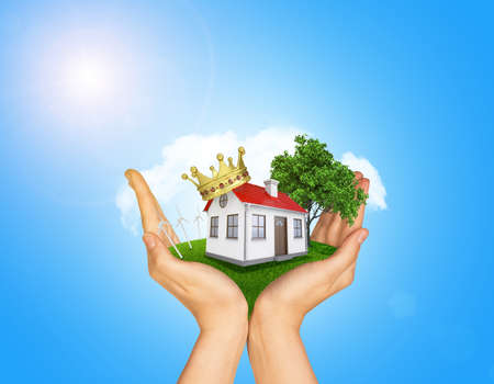 Hands holding house on green grass with crown, red roof, chimney, tree, wind turbine. Background clouds and blue sky photo