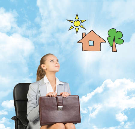 imagines: Business woman in skirt, blouse and jacket, sitting on chair and holding briefcase imagines house with tree. Against background of blue sky and clouds