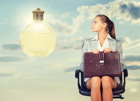 Business woman in skirt, blouse and jacket, sitting on chair and holding briefcase imagines perfume. Against background of sky and clouds photo