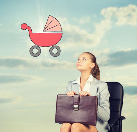imagines: Business woman in skirt, blouse and jacket, sitting on chair imagines buggy. Against background of sky and clouds Stock Photo