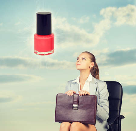 Business woman in skirt, blouse and jacket, sitting on chair imagines nail polish. Against background of sky and clouds photo