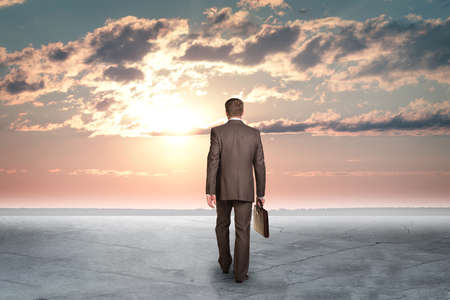 fissures: Concrete fissures surface. Man standing back. Sunset with fluffy clouds Stock Photo