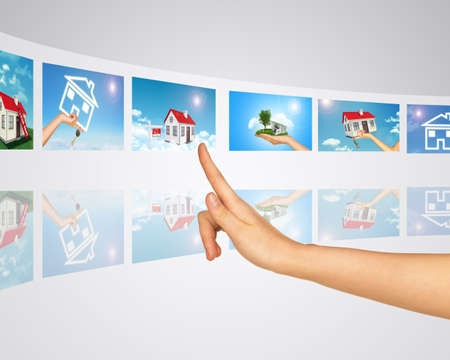 homes for sale: Finger presses one of virtual screens. Subject homes for sale and rent. Mirror reflection