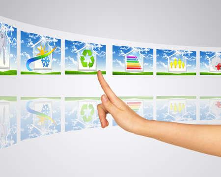 eficiencia energetica: Iconos edificios inteligentes. El dedo presiona una de las pantallas virtuales. Reflexión de espejo