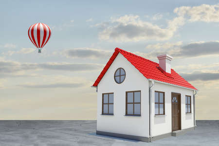 White house with red roof, brown door and chimney. Background sun shines brightly on large clouds