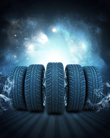 vulcanization: Wedge of new car wheels. Abstract blue background is night sky and stripes at bottom Stock Photo