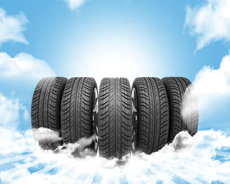 vulcanization: Wedge of new car wheels. Blue background is sky with clouds and stripes at bottom