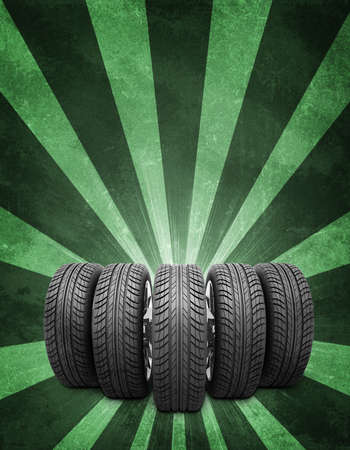 vulcanization: Wedge of new car wheels. Abstract green background is concrete surface and stripes at bottom