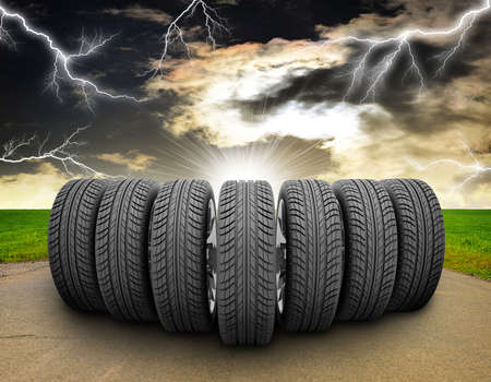 vulcanization: Wedge of new car wheels. Road, roadsides and grass field. Stormy sky with lightning in background Stock Photo