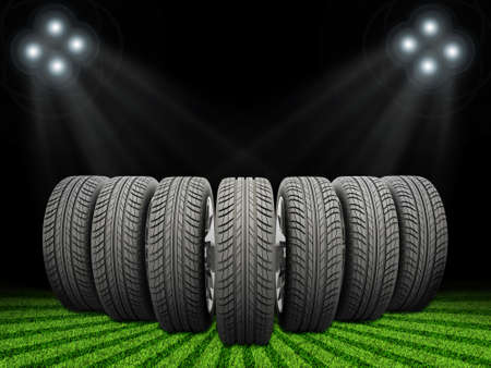 vulcanization: Wedge of new car wheels. Abstract background is green grass, stripes at bottom and spotlights